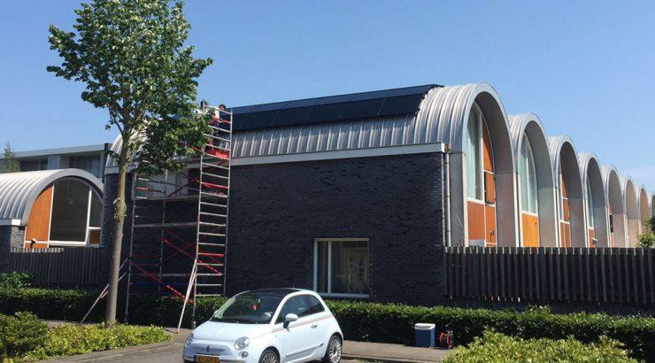 Een huis met zonnepanelen een witte auto